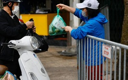 """Người dân phố Trúc Bạch nhận """"tiếp tế"""" thực phẩm qua rào chắn trong buổi đầu cách ly vì ca nhiễm Covid-19"""